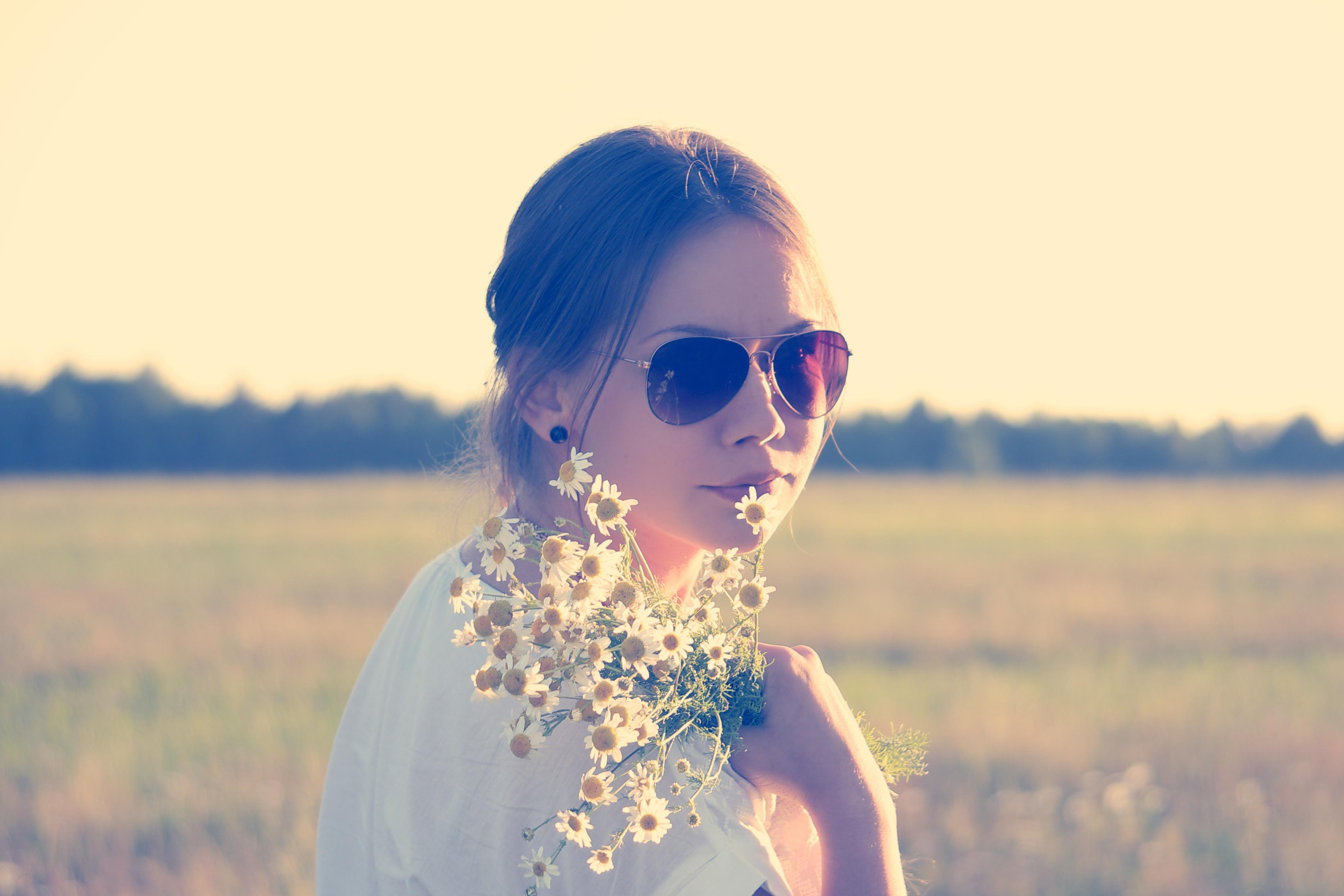 girl in sunglasses holding flowers