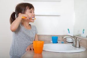 Cute girl brushing teeth